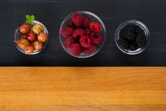 A place for inscription on a wooden surface, with three plates of black background with berries of raspberries, gooseberries, blac. A place for inscription on a Royalty Free Stock Image