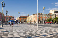 Place Massena in Nice, France. NICE, FRANCE - OCTOBER 2, 2014: People walking on Place Massena, main pedestrian square of the city. Modern statues on tall poles royalty free stock photography
