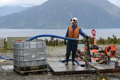 In place. MOANA, NEW ZEALAND, OCTOBER 27, 2017: An oil rigger pumps residual crude oil from an abandoned oil well in preparation for capping the well Stock Photography
