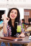 This place is OK. Woman showing OK sign in a restaurant Royalty Free Stock Image