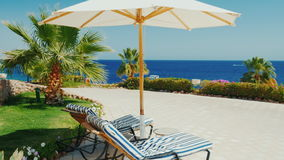 A place of paradise rest. Beach umbrella and blue sea on a sunny day. Crane shot stock video