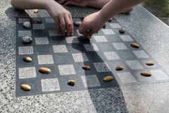 Chessboard for chess or outdoor checkers in the park. A place in the park to play in check or checkers. Outdoor fun in the park on a sunny spring day. He plays royalty free stock photos