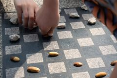 Chessboard for chess or outdoor checkers in the park. A place in the park to play in check or checkers. Outdoor fun in the park on a sunny spring day. He plays royalty free stock photography