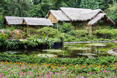 Peaceful chinese garden with bamboo shelters and large pond Stock Image