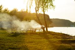 Concept of eating bbq outdoor during summer time. Place for a picnic outdoors, smoke from the brazier in the backlight, sunset on the shore of the lake. Concept stock photo