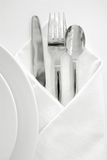 Place setting 1. Shiny silverware on white plate Royalty Free Stock Images