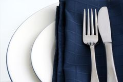 Place Setting. White plates with dark blue napkin and silver knife and fork, with white background stock images