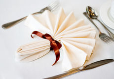 Place setting. White napkin and place setting with brown ribbon and flatware on a white tablecloth royalty free stock photo