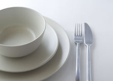 Place setting. Table place setting with bowl, two plates, fork and knife on white background royalty free stock photos
