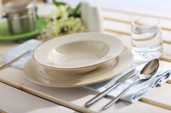Place Setting. Dinner Place Setting On A Garden Table with Silver Spoon And Knife, Blue Napkin And Plates stock images