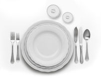 Place setting. With white china plates and metal cutlery royalty free stock photography