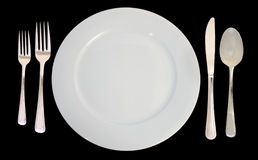 Place Setting. This is a place setting including one white dinner plate and silverware on a black background royalty free stock photos
