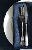 Place setting with blue napkin. White plate with cutlery and a dark blue napkin royalty free stock photography