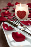 Place setting with candle. And cutlery for valentines day royalty free stock image