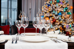 Place setting with Christmas tree in background Royalty Free Stock Photography