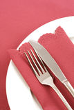 Place Setting with Dusky Pink Napkin. White plate, silver knife and fork, with dusky pink napkin and tablecloth stock image