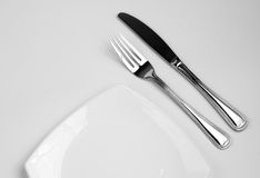 Place setting for one person. Knife, square white. Plate and fork stock photos
