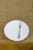 Place setting with plate and fork against brown plate mat Royalty Free Stock Photography