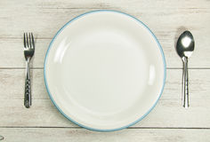 Place setting with plate,spoon,fork. Top view of place setting with plate, spoon and fork on wood table Royalty Free Stock Image
