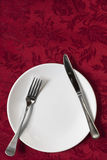 Place Setting on Red Brocade Tablecloth Stock Photo