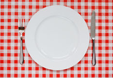 Place setting on red Gingham tablecoth. Empty plate setting with plate, knife and fork on red gingham background popular symbol for diners and cafes Royalty Free Stock Image