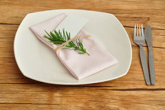 Place setting. A simple place setting consisting of a plate and a knife and fork with a napkin that is tied together an empty name card and a piece of a plant Stock Photos