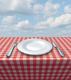 Place Setting Table. Place setting with a fork knife and white empty plate on a checkered red and white tablecloth on a summer blue sky as a food service and Stock Image