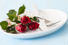 Place setting for valentines day. With three roses and cutlery Royalty Free Stock Photo