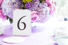 Place setting at wedding reception. Flower bouquet on laid table at wedding reception with number 6 seating arrangement card in foreground Stock Photography