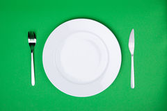 Place setting with white plate, fork and knife Stock Photo