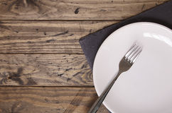 Place setting. White plate and fork on a wooden background Stock Images