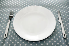 Place setting white plate and grey polka dot. Empty white dinner plate with ustensils on fun grey polka dot tablecloth Royalty Free Stock Images
