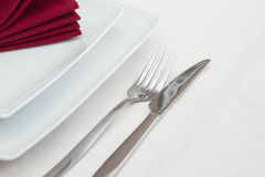 Place setting with white plates and red napkin Stock Photos