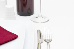 Place setting with white plates and red wine Royalty Free Stock Photos