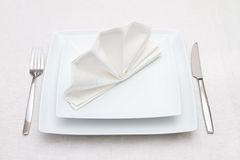 Place setting with white plates and white napkin Royalty Free Stock Images