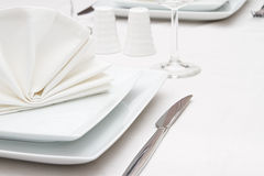Setting with white crockery and a wine glass Stock Photos