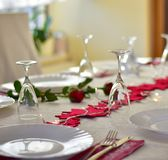 Party dinner table with red decoration. Place or table settings for party dinner or Valentine`s day or Christmas with red stars and red roses Royalty Free Stock Photo