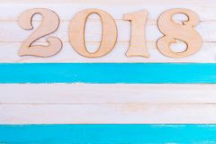 Place for text and New Year figures. Wooden figures on a white-blue background. Postcard for the winter holiday stock photography