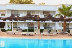 Place to relax by the pool with sun loungers and parasols stock photos