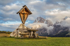 A place to rest beneath Jesus on the cross overlooking the beautiful rock massifs of the Dolomites. Royalty Free Stock Photos