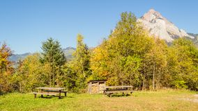 Canton Schwyz, Mythen. A place to rest for the tourists in the mountains. Wooden tables. Firewood for fire and grill. The top of the mountain in the background Royalty Free Stock Photos