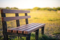 A lone bench in a field in the middle of the UK taken during a low sunset royalty free stock photo