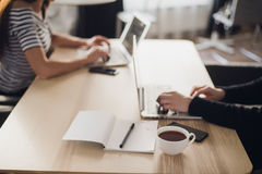 Place of work. Close-up shot of comfortable working place in office with wooden table and laptop coffee of cup smart. Phone notepad and mouse laying on it royalty free stock image