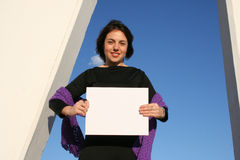 Place your ad here. Young woman holding a blank white sign Stock Photos