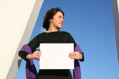Place your ad here. Young woman holding a blank white sign Stock Photo