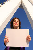 Place your ad here. Young woman holding a blank white sign Royalty Free Stock Photography