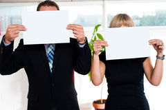 Place your business ad here. Boss and secretary each holding blank banner ad in front of their face Royalty Free Stock Photos