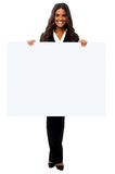 Place your business ad here. Attractive young woman holding blank banner ad Royalty Free Stock Images
