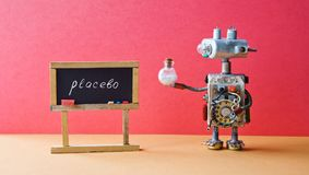 Placebo effect concept Medic robot drugs tube, black chalkboard with handwritten word placebo. Pink wall brown floor Stock Image