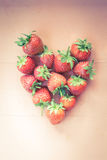 Placed red strawberry in heart shape, vintage tone Royalty Free Stock Photo
